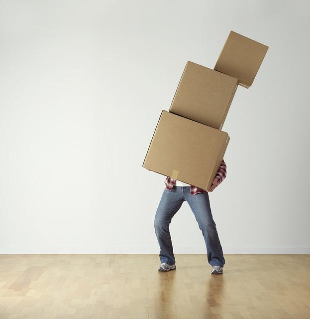 man balancing moving boxes.